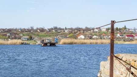 Ukraine, Southern Bug River - 2 avril 2017: traversée en ferry. Le ferry se déplace avec l'aide de la force musculaire d'un homme. Reforme le câble en acier. Un tel ferry est unique en Ukraine. Banque d'images