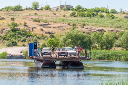 Ukraine, Southern Bug River - 4 juin 2017: traversée en ferry. Le ferry se déplace avec l'aide de la force musculaire d'un homme. Reforme le câble en acier. Un tel ferry est unique en Ukraine. Banque d'images - 84459830
