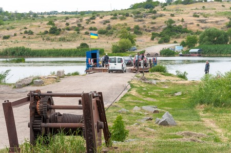 Ukraine, Southern Bug River - 18 juin 2017: traversée en ferry. Dispositif de réglage et de fixation d'un câble en acier pour un ferry de rivière. Un tel ferry est unique en Ukraine. Banque d'images - 84620460