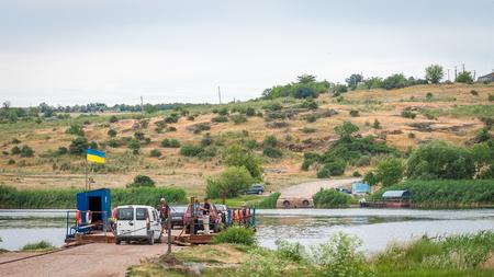 Ukraine, Southern Bug River - 18 juin 2017: traversée en ferry. Le ferry se déplace avec l'aide de la force musculaire d'un homme. Reforme le câble en acier. Un tel ferry est unique en Ukraine. Banque d'images - 84459832