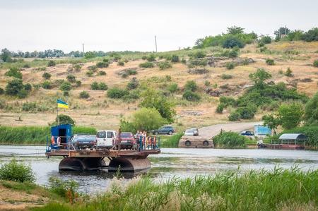 Ukraine, Southern Bug River - 18 juin 2017: traversée en ferry. Le ferry se déplace avec l'aide de la force musculaire d'un homme. Reforme le câble en acier. Un tel ferry est unique en Ukraine. Banque d'images - 84459833