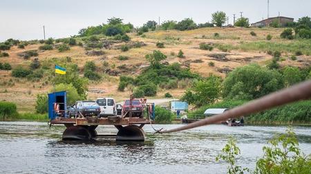Ukraine, Southern Bug River - 18 juin 2017: traversée en ferry. Le ferry se déplace avec l'aide de la force musculaire d'un homme. Reforme le câble en acier. Un tel ferry est unique en Ukraine. Banque d'images - 84459837