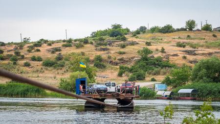 Ukraine, Southern Bug River - 18 juin 2017: traversée en ferry. Le ferry se déplace avec l'aide de la force musculaire d'un homme. Reforme le câble en acier. Un tel ferry est unique en Ukraine. Banque d'images - 84459838
