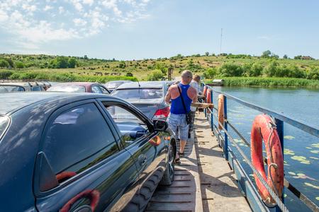 Ukraine, Southern Bug River - 4 juin 2017: traversée en ferry. Le ferry se déplace avec l'aide de la force musculaire d'un homme. Reforme le câble en acier. Un tel ferry est unique en Ukraine. Banque d'images - 84459843