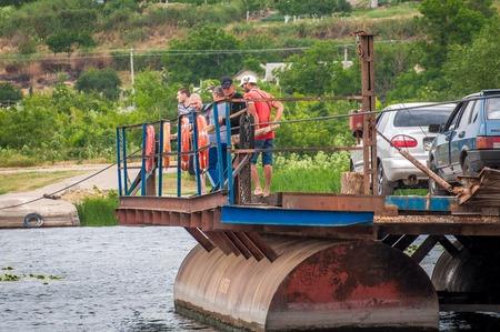 Ukraine, Southern Bug River - 18 juin 2017: traversée en ferry. Le ferry se déplace avec l'aide de la force musculaire d'un homme. Reforme le câble en acier. Un tel ferry est unique en Ukraine. Banque d'images - 84459920