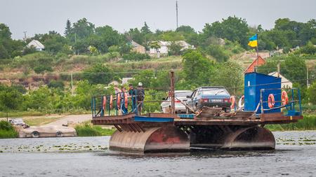Ukraine, Southern Bug River - 18 juin 2017: traversée en ferry. Le ferry se déplace avec l'aide de la force musculaire d'un homme. Reforme le câble en acier. Un tel ferry est unique en Ukraine. Banque d'images - 84459943