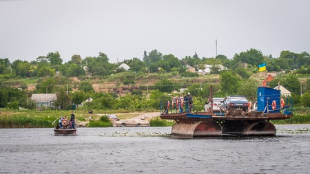 Ukraine, Southern Bug River - 18 June 2017: Ferry crossing. The ferry moves with the help of a mans muscular strength. Repels from the steel cable. Such a ferry is unique in Ukraine.