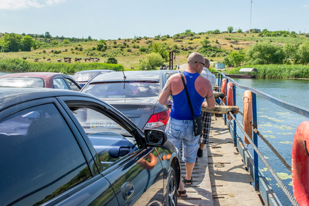 Ukraine, Southern Bug River - 4 juin 2017: traversée en ferry. Le ferry se déplace avec l'aide de la force musculaire d'un homme. Reforme le câble en acier. Un tel ferry est unique en Ukraine. Éditoriale