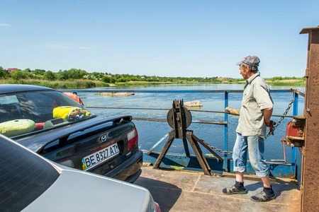 L'Ukraine, le Southern Bug River - 4 juin 2017: passage à niveau. Le ferry se déplace par la force musculaire de l'homme. Reforme le câble en acier. Le ferryman déplace cet objet flottant. Banque d'images - 84459987