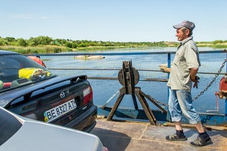 L'Ukraine, le Southern Bug River - 4 juin 2017: passage à niveau. Le ferry se déplace par la force musculaire de l'homme. Reforme le câble en acier. Le ferryman déplace cet objet flottant. Banque d'images - 84460004