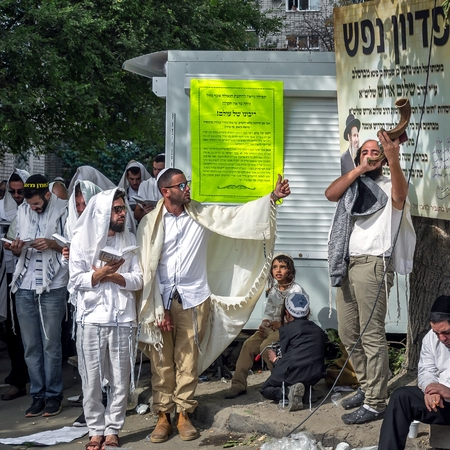 Uman, Ukraine - 21 September 2017: Rosh Hashanah, Jewish New Year. Mass prayer of pilgrims of Hasidim on the street where Rebbe Nachman, the founder of Hasidism, is buried. Jewish hasid blows Shofar.