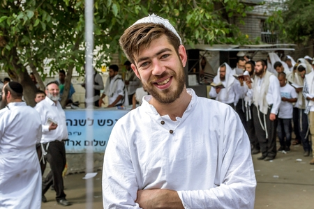 A young Hasid against the background of a pilgrims prayer. Uman, Ukraine - 21 September 2017: Rosh Hashanah, Jewish New Year 5778. It is celebrated near the grave of Rabbi Nachman in Uman.