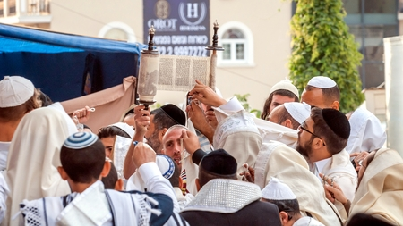 Hasids pray while reading the Torah scroll. Uman, Ukraine - 21 September 2017: Rosh Hashanah, Jewish New Year. It is celebrated near the grave of Rabbi Nachman in Uman.