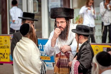 A group of Hasidim pilgrims in traditional clothing emotionally talk. Uman, Ukraine - September 21, 2017: Rosh hashanah holiday, Jewish New Year.