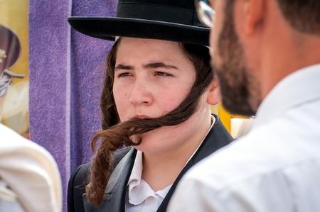 Un jeune Hasid dans un chapeau traditionnel juif et avec de longs payos. Uman, Ukraine - 21 septembre 2017: Rosh Hashanah, Nouvel An juif. Éditoriale