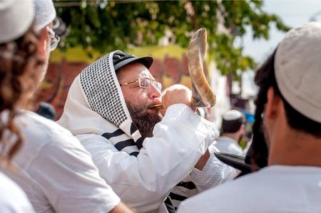 Jewish hasid blows Shofar. Uman, Ukraine - 21 September 2017: Rosh Hashanah, Jewish New Year. Editorial