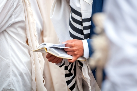 Hands and prayer book close-up. Orthodox hassidic Jews pray in a holiday robe and tallith. Stock Photo