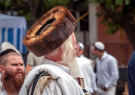 Hasid in the traditional headgear shtreimel on the street in a crowd of pilgrims. Uman, Ukraine - 21 September 2017: Rosh Hashanah, Jewish New Year