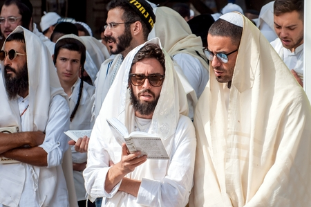 Mass prayer. Hasids pilgrims in traditional clothes. Tallith - jewish prayer shawl. Uman, Ukraine - 21 September 2017: Rosh Hashanah, Jewish New Year.