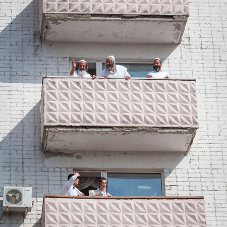 Pilgrims of Hasidi on the balcony of the high-rise building are having fun celebrating the holiday of Rosh-ha-Shana. Uman, Ukraine - September 21, 2017: Jewish New Year.