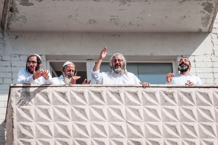 Pilgrims of Hasidi on the balcony of the high-rise building are having fun celebrating the holiday of Rosh-ha-Shana. Uman, Ukraine - September 21, 2017: Jewish New Year.