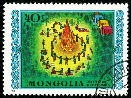 Ukraine - circa 2018: A postage stamp printed in Mongolia shows drawing Scout Camp. The children are sitting around the fire. Series: International Children Day. Circa 1976.