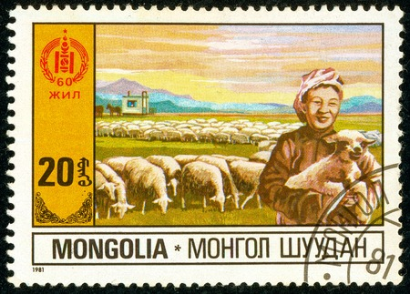 Ukraine - circa 2018: A postage stamp printed in Mongolia shows Sheep Farming. A woman is holding a lamb in her hands. Herd of sheep. Series: 60 Years of Independence. Circa 1981.