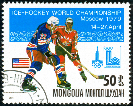 Ukraine - circa 2018: A postage stamp printed in Mongolia show hockey with the puck. A players in the uniform of U.S.A., Canada. Flag U.S.A. Series: Moscow ice hockey world championships. Circa 1979. Banque d'images - 94167962