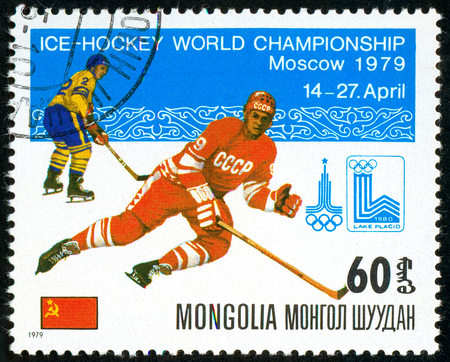 Ukraine - circa 2018: A postage stamp printed in Mongolia show hockey with the puck. A player in the uniform of USSR. Flag USSR. Series: Moscow ice hockey world championships. Circa 1979. Banque d'images - 94167967