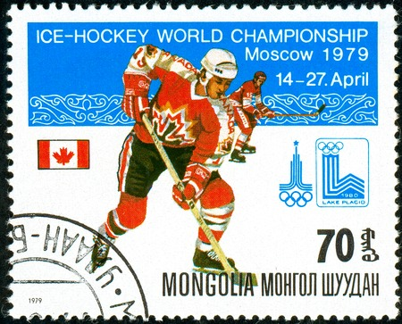 Ukraine - circa 2018: A postage stamp printed in Mongolia show hockey with the puck. A player in the uniform of Canada. Flag Canada. Series: Moscow ice hockey world championships. Circa 1979. Banque d'images - 94167970
