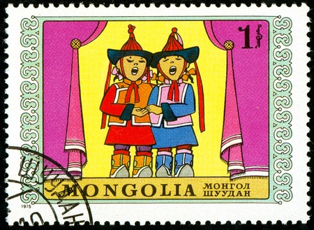 Ukraine - circa 2018: A postage stamp printed in Mongolia show two children in Mongolian national clothes sing. Series: International Childrens Day. Circa 1975.