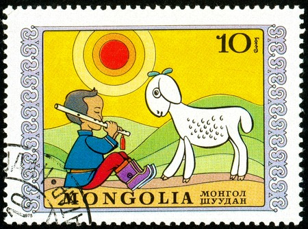 Ukraine - circa 2018: A postage stamp printed in Mongolia show Shepherd. A child sitting in a meadow plays a pipe - sheep listens. Series: International Childrens Day. Circa 1975. Banque d'images - 94168102