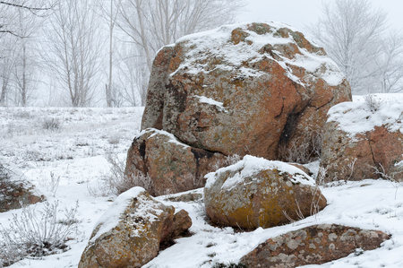 View of a large stone boulder. Frost. Fog. In the background, the trees are covered with frost. Soft focus. Banque d'images - 94037737