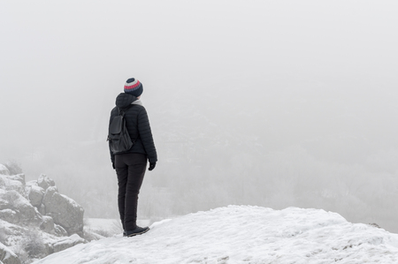 The girl on a frosty winter day is standing on a snow-covered rock and staring into the distance. Fog. Soft focus