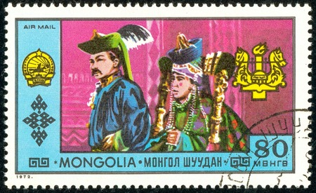 Ukraine - circa 2018: A postage stamp printed in Mongolia show A man and a woman in a traditional Mongolian bright, colorful suit. Series: National Achievements. Circa 1972. Editorial