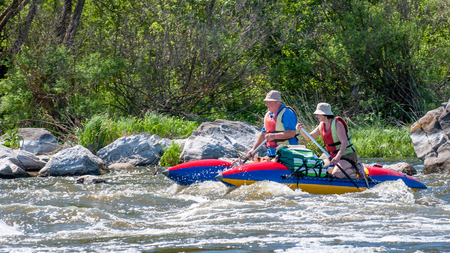 Myhiya, Ukraine - May 1, 2018: Rafting, kayaking. A married couple aged sailing on a rubber inflatable boat. Water splashes close-up. Extreme vacation. Ecological water tourism. Editorial