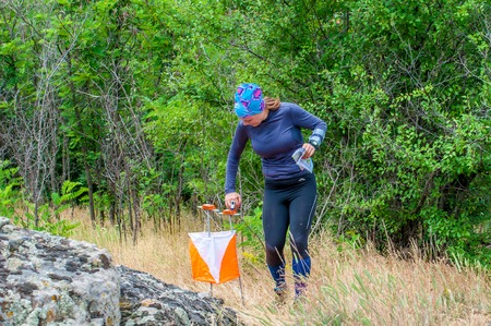 Yuzhnoukrainsk, Ukraine - May 26, 2018: Orienteering. Traditional annual orienteering game Partisan Spark Cup 2018. The athlete marks the passage of the control point