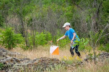 Yuzhnoukrainsk, Ukraine - May 26, 2018: Orienteering. Traditional annual orienteering game Partisan Spark Cup 2018. Young athlete marks the passage of the control point