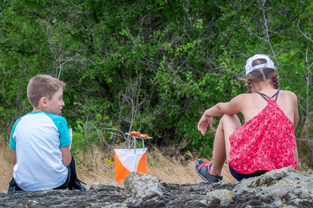 Yuzhnoukrainsk, Ukraine - May 26, 2018: Orienteering race. Annual orienteering game Partisan Spark Cup 2018. The young boy and girl are sitting near the control point watching the competitions.