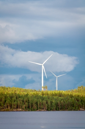Wind turbines, converting the wind's kinetic energy into electrical energy - ecologically clean source of renewable energy. Green energy in the green Finnish forest.