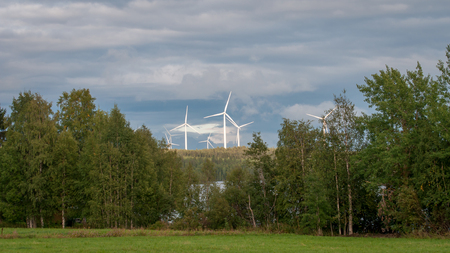 Wind turbines, converting the wind's kinetic energy into electrical energy - ecologically clean source of renewable energy. Green energy in the green Finnish forest. Banque d'images - 111063865