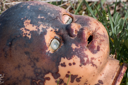 Creepy old doll head. Broken abandoned damaged scary toy in a garbage dump close-up. In the toy, the eye and mouth are damaged. The concept of fear, horror, crime. Very scary. 版權商用圖片