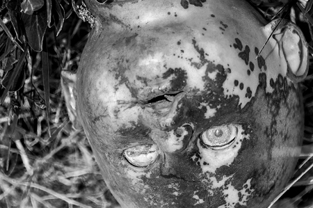 Creepy old doll head. Broken abandoned damaged scary toy in a garbage dump close-up. In the toy, the eye and mouth are damaged. The concept of fear, horror, crime. Very scary.
