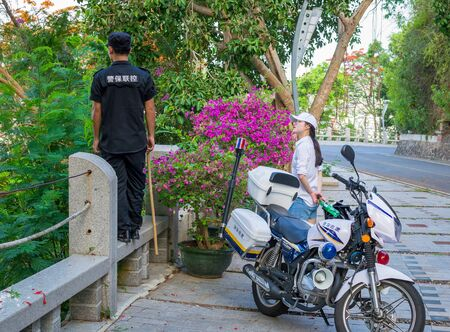 Hainan, Sanya, China - May 16, 2019. In a place where monkeys appear on the road and interfere with the movement, a policeman on a motorcycle periodically arrives and pushes them away with a stick