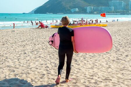 Surfing. Young girl with a surfboard goes on the beach. Extreme water sports. Healthy active lifestyle. Summer vacation