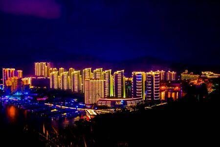 View of the night city of Sanya. Hainan Island, China. Neon lights of the night metropolis