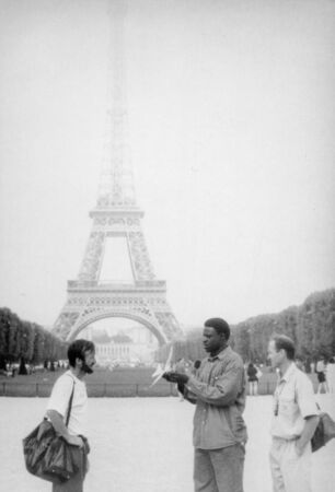 Paris, old black and white photo, august 1994. A black street vendor is trying to sell a toy airplane to Ukrainian tourists. On the background Eiffel Tower
