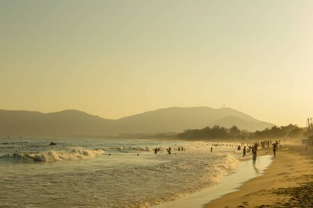 Tropical beach, people having fun in the sea, the golden twilight of sunset light. Soft focus Stock Photo