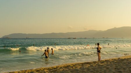 Tropical beach, people having fun in the sea, golden twilight of sunset light. Soft focus. A young girl in a closed bathing suit stands on the shore and looks into the distance