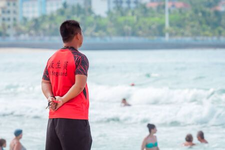 A Chinese lifeguard on Sanya beach keeps order and safety. In the hands of a whistle to ensure the discipline of tourists on the water. T-shirt with the inscription Lifeguard in English and Chinese. Stock Photo